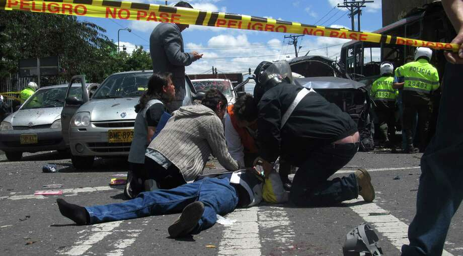 Pedestrians assist a man who was wounded when a bomb exploded in Bogota, Colombia, Tuesday, May 15, 2012. Colombian President Juan Manuel Santos says two people were killed in the bomb attack. Photo: John Ramirez, Associated Press / AP