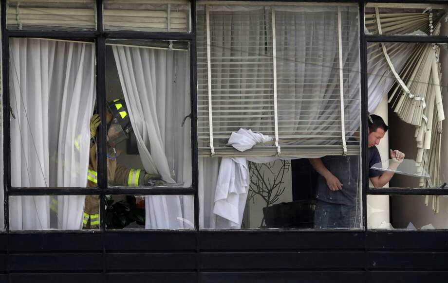A firefighter inspects a shop's windows that were damaged by a bomb explosion in Bogota, Colombia, Tuesday, May 15, 2012. Photo: Fernando Vergara, Associated Press / AP