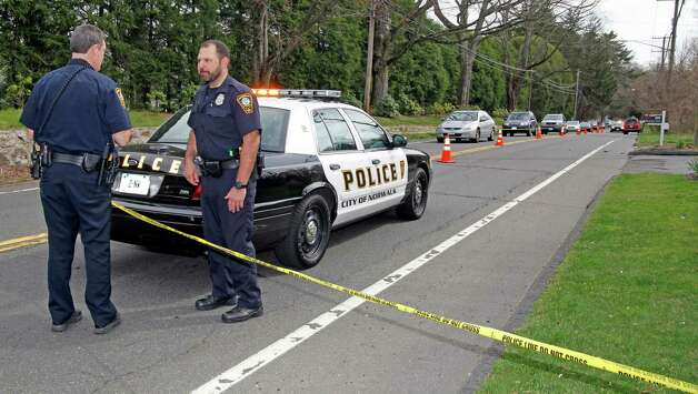 In this March 24, 2012, photo, Norwalk, Conn., police stand at the scene of an accident on New Canaan Avenue where Kenneth Dorsey, 43, of Norwalk was fatally struck by an SUV while he was jogging. A 16-year-old girl from New Canaan, Conn., who police say was driving the SUV, turned herself in May 12, 2012, after learning there was a warrant out for her arrest on charges of negligent homicide with a motor vehicle. Photo: Danielle Robinson, The Hour, Danielle Robinson Via AP / Associated Press