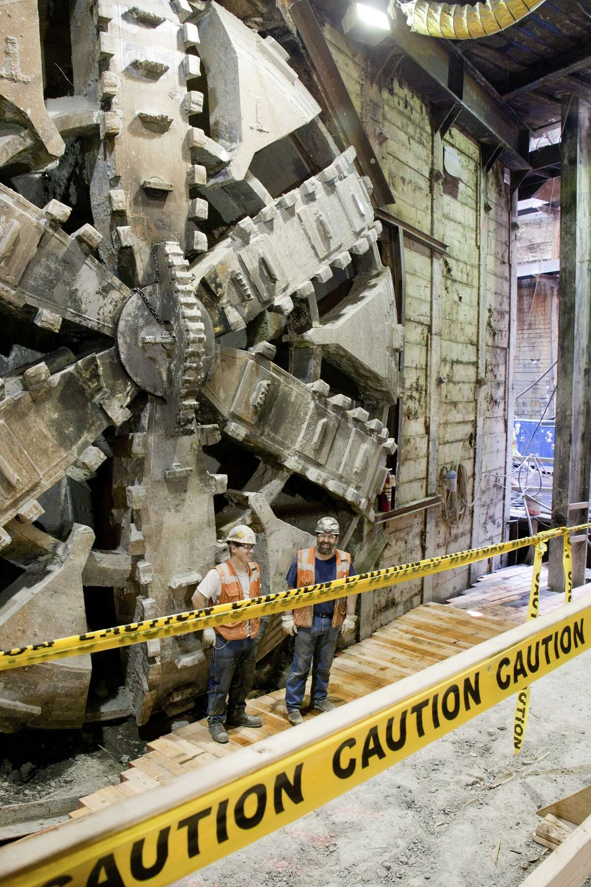 """Two workers on the U-Link light rail project stand near """"Brenda,"""" the 21-foot diameter tunneling machine that completed its one-mile trip on the second tunnel between a future Capitol Hill light rail station and downtown."""