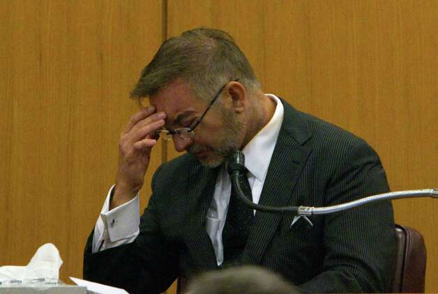 Former hand surgeon Michael Brown bows his head on the stand during a divorce trial with estranged wife Rachel Brown in the 309th Court of the Harris County Family Law Center Tuesday, May 15, 2012, in Houston. (Cody Duty / Houston Chronicle) Photo: Cody Duty / © 2011 Houston Chronicle