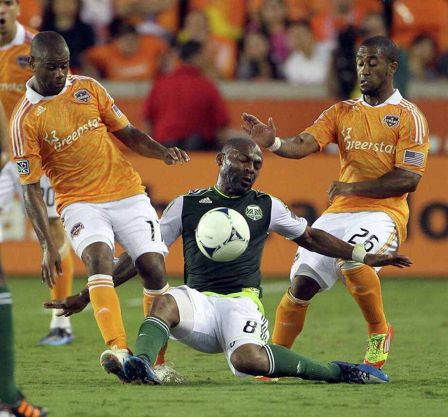 Portland Timber midfielder Franck Songo'o gets bottle necked by Dynamo's Corey Ashe. ( Nick de la Torre / Houston Chronicle ) Photo: Nick De La Torre, Houston Chronicle / © 2012  Houston Chronicle