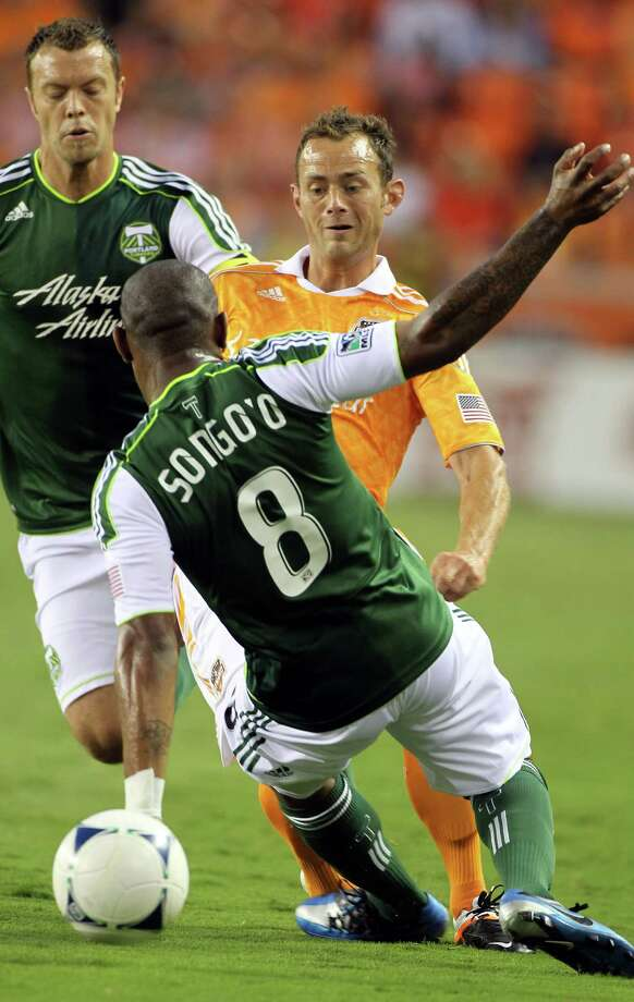 Dynamo midfielder Brad Davis looks to advance the ball past Portland Timber midfielder Franck Songo'o. Photo: Nick De La Torre, Houston Chronicle / © 2012  Houston Chronicle