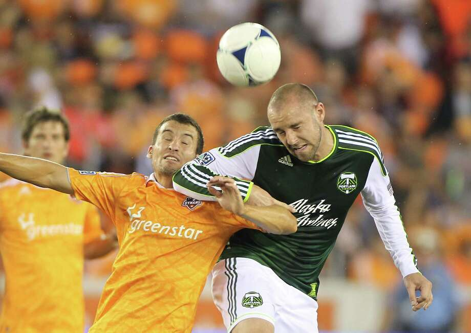 Dynamo midfielder Nathan Sturgis, left, battles Portland Timber forward Kris Boyd for the ball. Photo: Nick De La Torre, Houston Chronicle / © 2012  Houston Chronicle