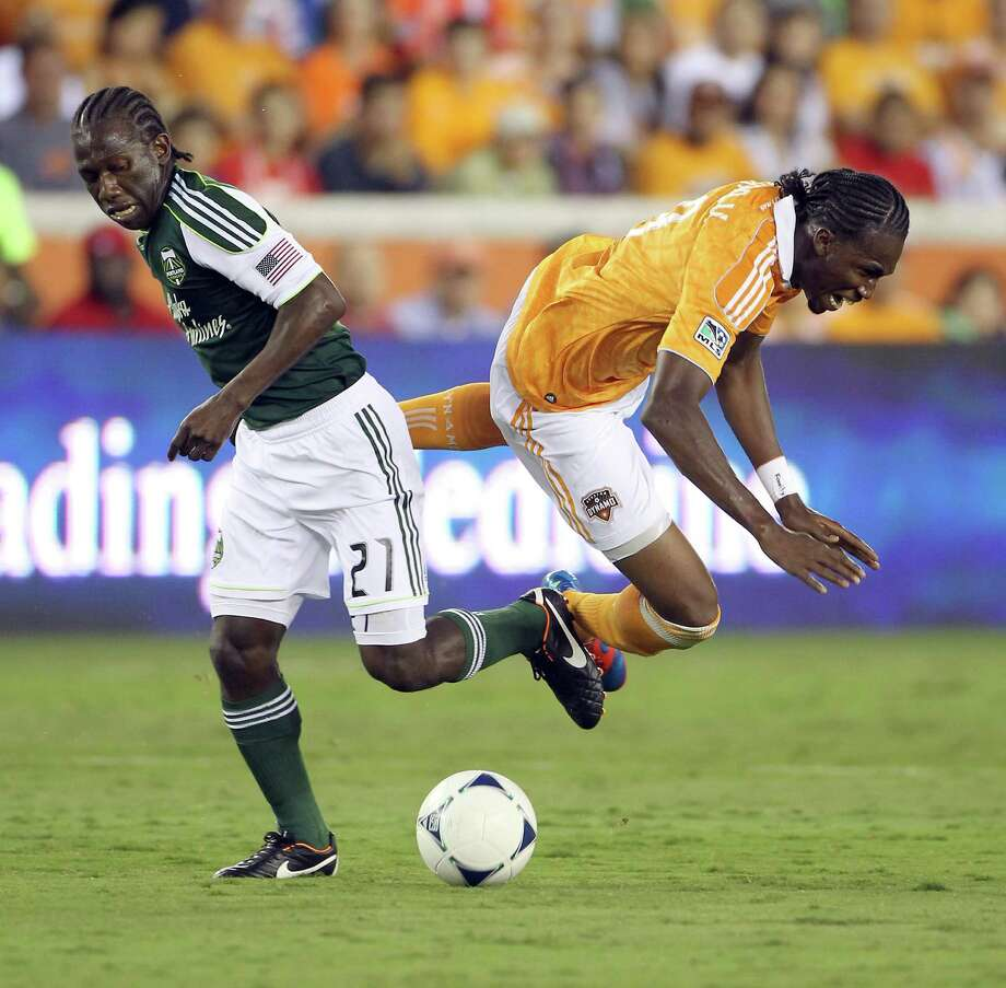 Portland Timber defender Chris Taylor, left, collides with Houston Dynamo forward Macoumba Kandji. Photo: Nick De La Torre, Houston Chronicle / © 2012  Houston Chronicle
