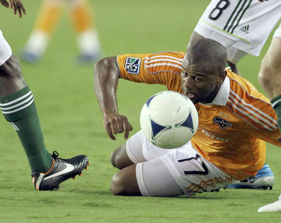 Houston Dynamo midfielder Luiz Camargo looks to keep the ball in a forest of Portland Timber feet during the first half of a Major League Soccer match, Tuesday, May 15, 2012, in BBVA Compass Stadium in Houston. Photo: Nick De La Torre, Houston Chronicle / © 2012  Houston Chronicle