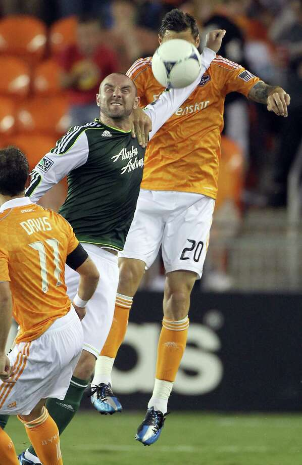 Portland Timber forward Kris Boyd, middle, keeps Houston Dynamo defender Geoff Cameron at bay as he heads a goal kick. Photo: Nick De La Torre, Houston Chronicle / © 2012  Houston Chronicle