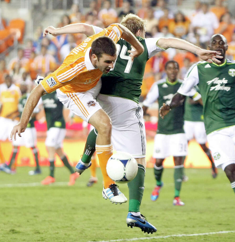 Dynamo forward Will Bruin, left, struggles to get past the Timbers' Steven Smith during the second half of Tuesday night's defense-dominated standoff. Photo: Nick De La Torre / © 2012  Houston Chronicle
