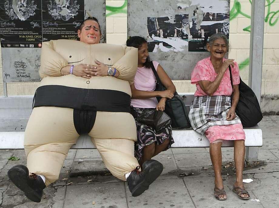 A pseudo sumohogs a bench during a clown parade in San Salvador, El Salvador. Photo: Luis Romero, Associated Press