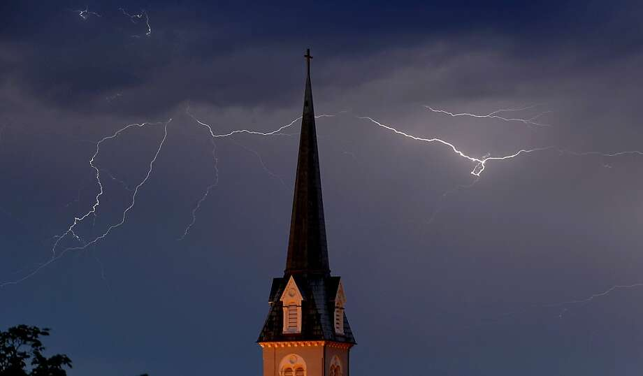 Lightening flashes across the sky behind the steeple of St. George's Episcopal Church as storms roll through the area on Tuesday evening, May 15, 2012, in Fredericksburg, Va. (AP Photo/The Free Lance-Star, Reza A. Marvashti) Photo: Reza A. Marvashti, Associated Press