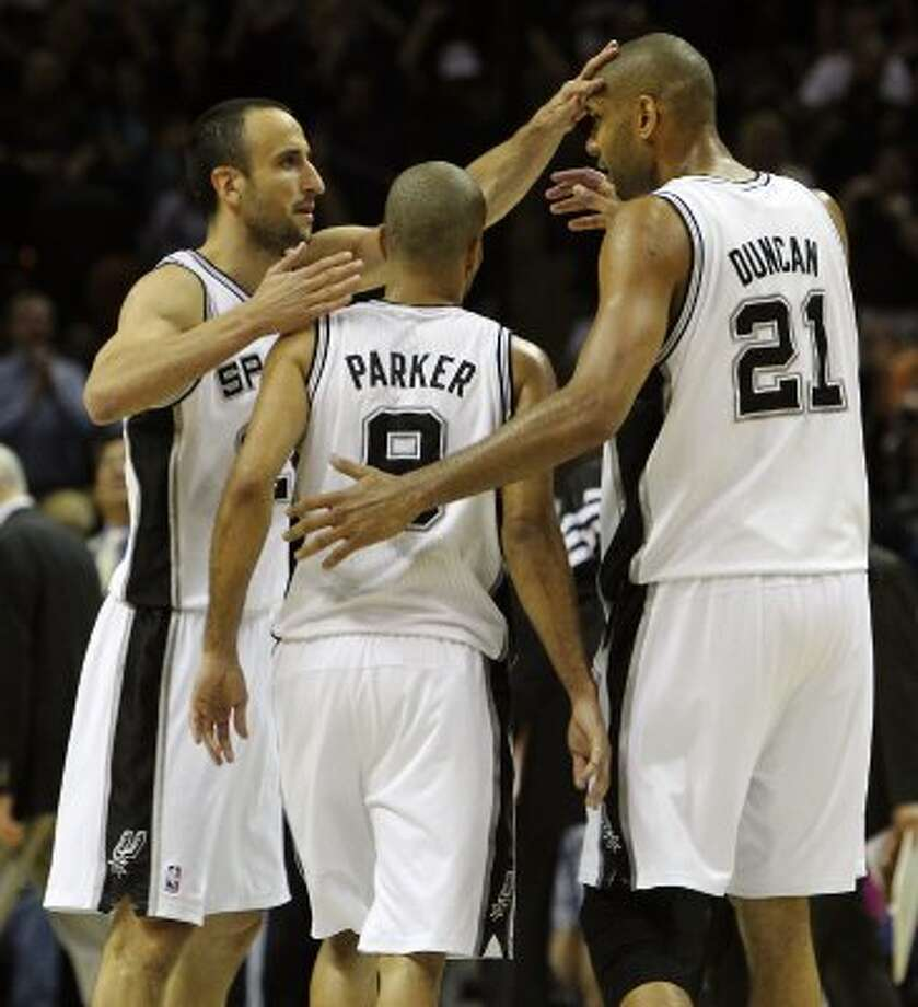 Spurs' Manu Ginobili (20) taps teammate Tim Duncan (21) on the head as the with Tony Parker (09) head to the bench after a timeout in the game against the Los Angeles Clippers in the second half of Game 1 of the Western Conference semi-finals at the AT&T Center on Tuesday, May 15, 2012. Spurs defeated the Clippers, 108-92. Kin Man Hui/Express-News. (Kin Man Hui / SAN ANTONIO EXPRESS-NEWS)