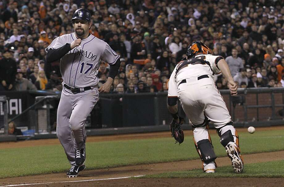 Colorado Rockies' Todd Helton (17) scores on a sacrifice fly hit by Jordan Pacheco past San Francisco Giants catcher Buster Posey during the sixth inning of a baseball game in San Francisco, Tuesday, May 15, 2012. (AP Photo/Jeff Chiu) Photo: Jeff Chiu, Associated Press