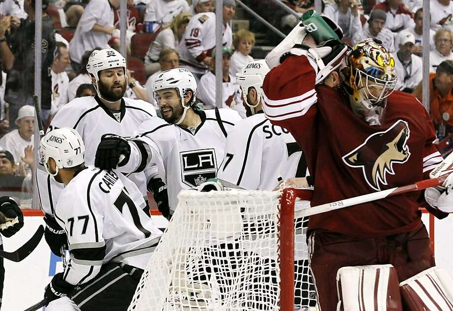 As Phoenix Coyotes goalie Mike Smith, far right, sprays water on his neck, Los Angeles Kings' Drew Doughty (8) celebrates with Rob Scuderi (7), Dustin Penner (25) and Jeff Carter (77) after a goal by Carter in the second period during Game 2 of the NHL hockey Stanley Cup Western Conference finals, Tuesday, May 15, 2012, in Glendale, Ariz. (AP Photo/Ross D. Franklin) Photo: Associated Press