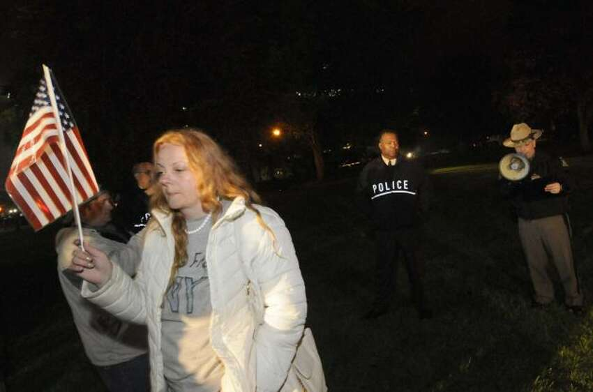 Protestor Joanne Farrell is warned by police to leave the park at the 11pm curfew in Lafayette Park in Albany N.Y. Tuesday May 1, 2012. (Michael P. Farrell/Times Union)