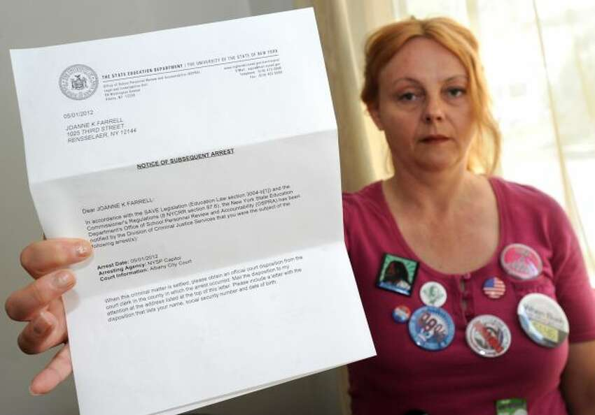 Joanne Farrell holds a letter she received from the Department of Education at her home Friday, May 11, 2012 in Rensselaer, N.Y. The letter is notifying her that her arrest at last week's Occupy Albany protests has red-flagged her fingerprints at the state Education Department. She works as a substitute teacher.(Lori Van Buren / Times Union)