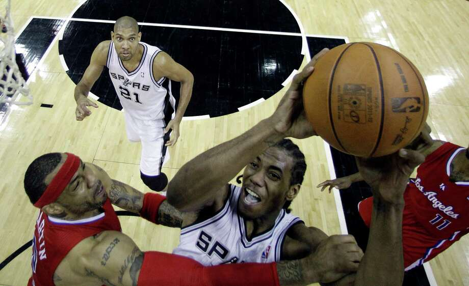 San Antonio Spurs' Kawhi Leonard, right, is defended by  Los Angeles Clippers' Kenyon Martin, left, during the third quarter of Game 1 of an NBA basketball Western Conference semifinal playoff series, Tuesday, May 15, 2012, in San Antonio. San Antonio won 108-92. (AP Photo/Eric Gay) Photo: Eric Gay, Associated Press / AP