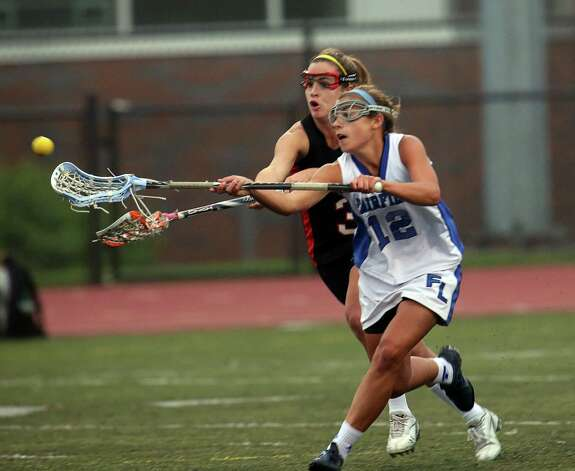 Fairfield Ludlowe Senior #12 Mary Deliberti fights for the ball against Fairfield Warde's # 3 Caroline Lambert in the crosstown lacrosse matchup on Tuesday, May 15, 2012. Fairfield Ludlowe High School won the contest 15-3. Photo: Mike Ross / Connecticut Post Freelance © www.mikerossphoto.com