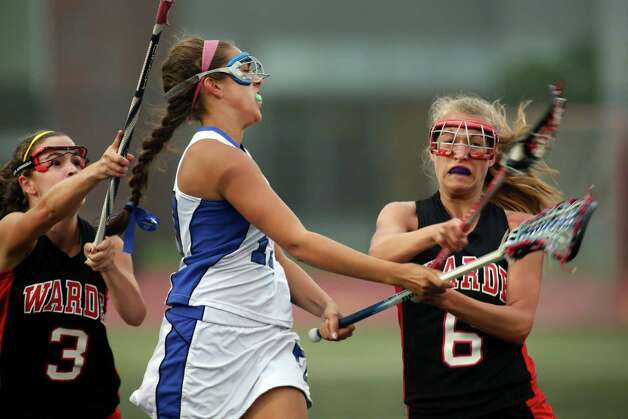 Fairfield Ludlowe Senior #10 Julia Tomeo passes the ball to teammate while getting pressured from Fairfield Warde's # 3 Caroline Lambert and #6 Jen Jacob during first period action in the crosstown lacrosse matchup on Tuesday, May 15, 2012. Fairfield Ludlowe High School won the contest 15-3. Photo: Mike Ross / Connecticut Post Freelance © www.mikerossphoto.com