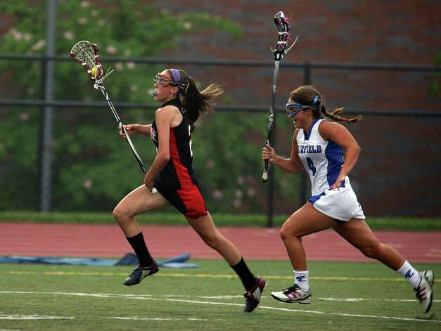 Fairfield Warde #2 Katie Tangney  runs upfield with the ball as Fairfield Ludlowe #4 Lizzy Pratt gives chase during first period action in the crosstown lacrosse matchup on Tuesday, May 15, 2012. Fairfield Ludlowe High School won the contest 15-3. Photo: Mike Ross / Connecticut Post Freelance © www.mikerossphoto.com