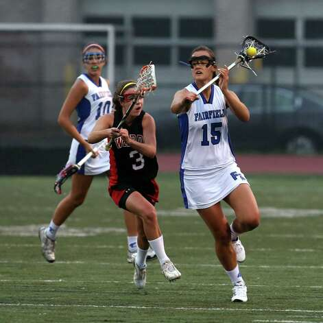 Fairfield Ludlowe Senior #15 Sarah Nesi looks to pass as Fairfield Warde's # 3 Caroline Lambert gives chase in the crosstown lacrosse matchup on Tuesday, May 15, 2012. Fairfield Ludlowe High School won the contest 15-3. Photo: Mike Ross / Connecticut Post Freelance © www.mikerossphoto.com