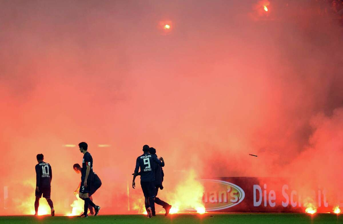 Fans of Berlin throw flares on the pitch next to Andre Mijatovic and Raffael of Berlin during the Bundesliga Relegation second leg match between Fortuna Duesseldorf and Hertha BSC Berlin at Esprit-Arena on Tuesday in Duesseldorf, Germany.