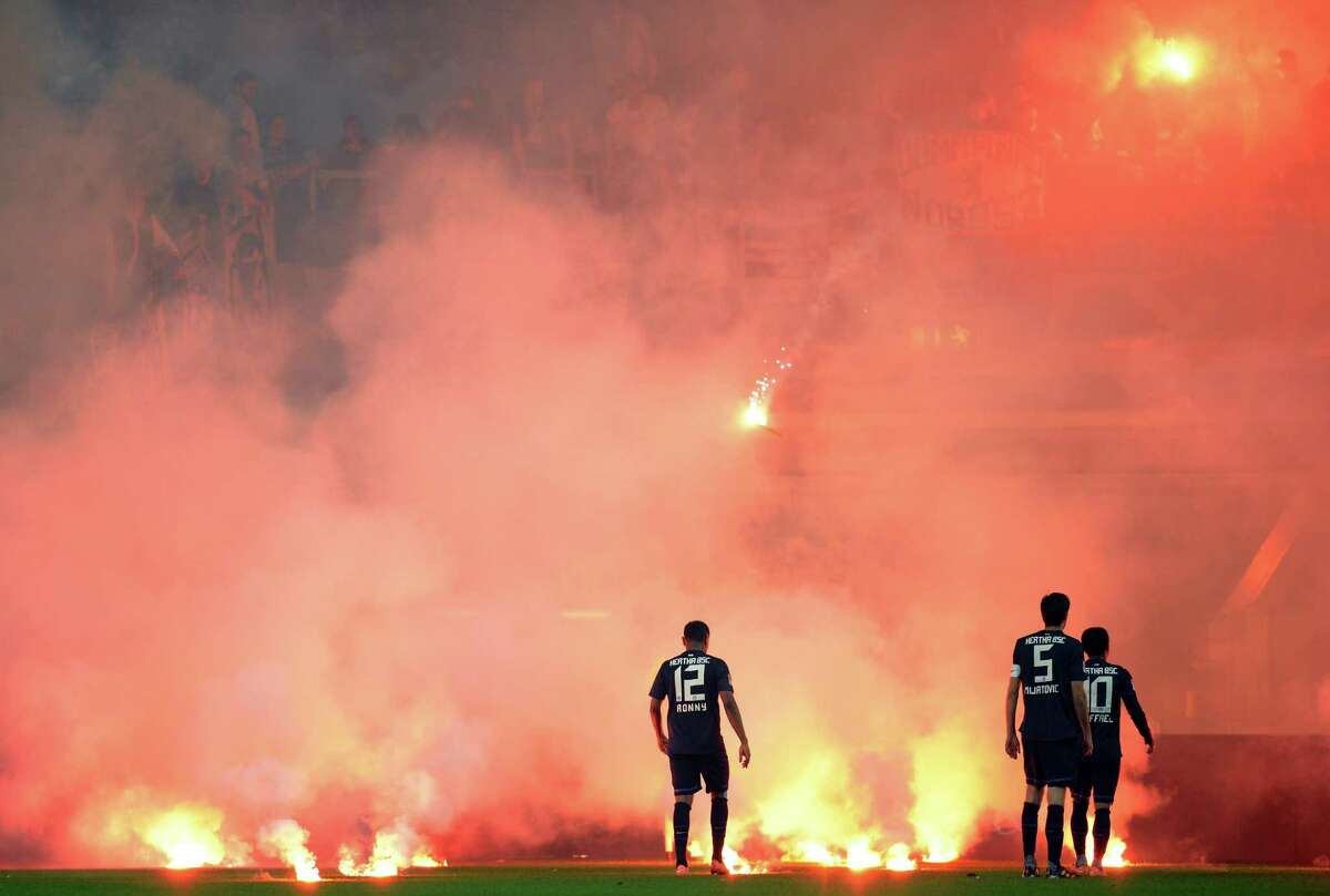 Fans of Berlin throw flares on the pitch next to Ronny, Andre Mijatovic and Raffael of Berlin during the Bundesliga Relegation second leg match between Fortuna Duesseldorf and Hertha BSC Berlin at Esprit-Arena on Tuesday in Duesseldorf, Germany.