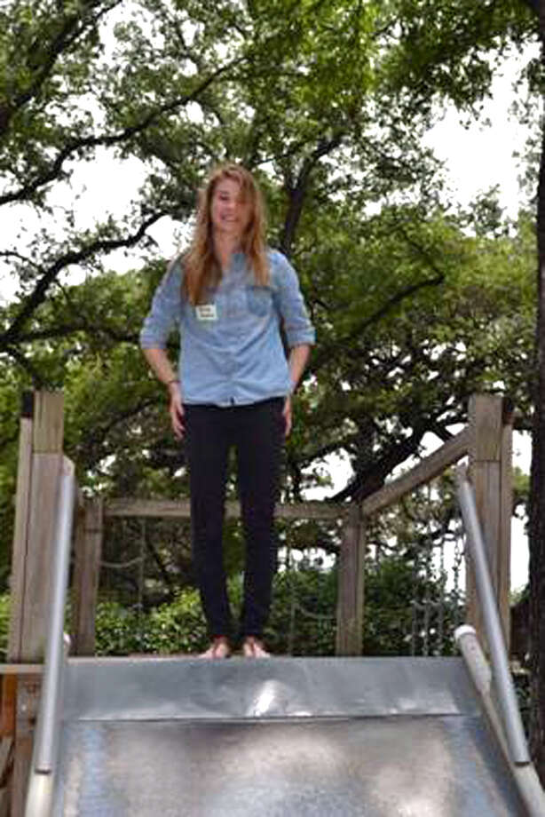 Now:Caroline Howard stands atop her favorite slide at her high school senior reunion for the Acorn school grads in May of 2012 Photo: COURTESY