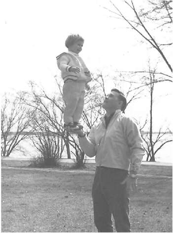 THEN: Paige Bird, 2, stands in the hand of dad, Clarke in 1964. Photo: COURTESY