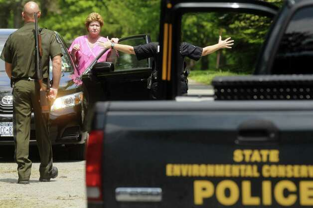 A women is ushered away by law enforcement as she stops to get a closer look at a bear perched in a tree napping off Meadow Drive in North Greenbush N.Y. Tuesday May 15, 2012. (Michael P. Farrell/Times Union) Photo: Michael P. Farrell