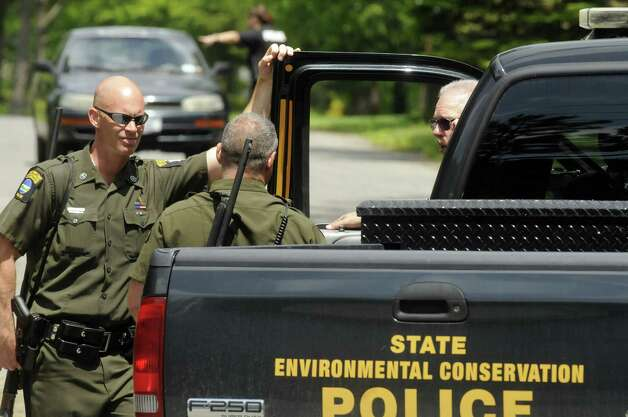 State Environmental Conservation Police talk as they wait out a bear perched in a tree napping off Meadow Drive in North Greenbush N.Y. Tuesday May 15, 2012. (Michael P. Farrell/Times Union) Photo: Michael P. Farrell