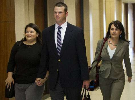 Former Houston police officer Andrew Blomberg, center, arrives to court during his trial Wednesday, May 16, 2012, in Houston. Blomberg is on trial for official oppression in the video taped 2010 beating of 15-year-old Chad Holley. The jury began deliberations in the case Tuesday. ( Brett Coomer / Houston Chronicle )