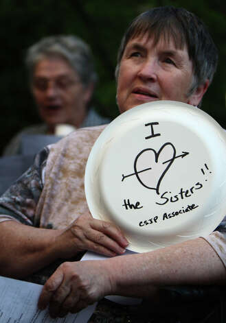 "Sue Nies holds a sign during a vigil offering support for Catholic nuns at St. James Cathedral in Seattle. Seattle Archbishop Peter Sartain has been appointed by the Pope to impose discipline on American nuns that the Vatican says sometimes promote ""radical feminist themes incompatible with the Catholic Faith."" Photo: JOSHUA TRUJILLO / SEATTLEPI.COM"