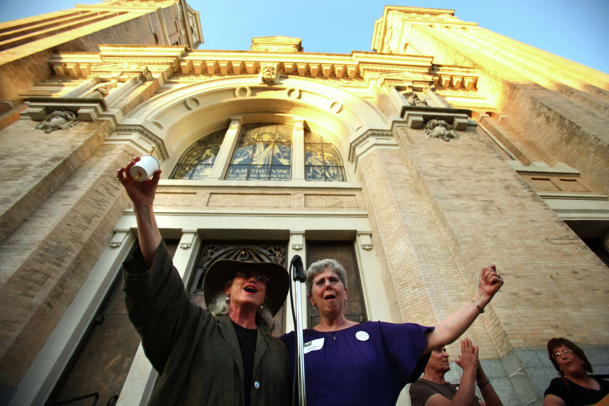 MHB Conant, left, and Gretchen Gundrum sing during a vigil offering support for Catholic nuns on Tuesday, May 15, 2012 at St. James Cathedral in Seattle. Seattle Archbishop Peter Sartain has been appointed by the Pope to impose discipline on American nuns that the Vatican says sometimes promote