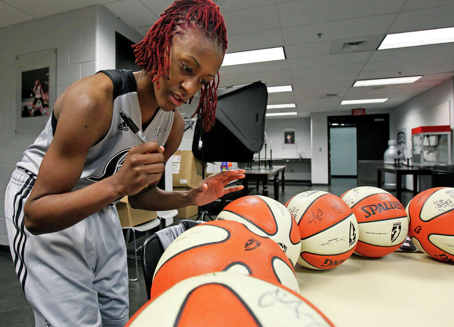 Point guard Danielle Robinson signs basketballs at the Silver Stars' media day on Wednesday at the AT&T Center. Photo: TOM REEL, San Antonio Express-News / San Antonio Express-News