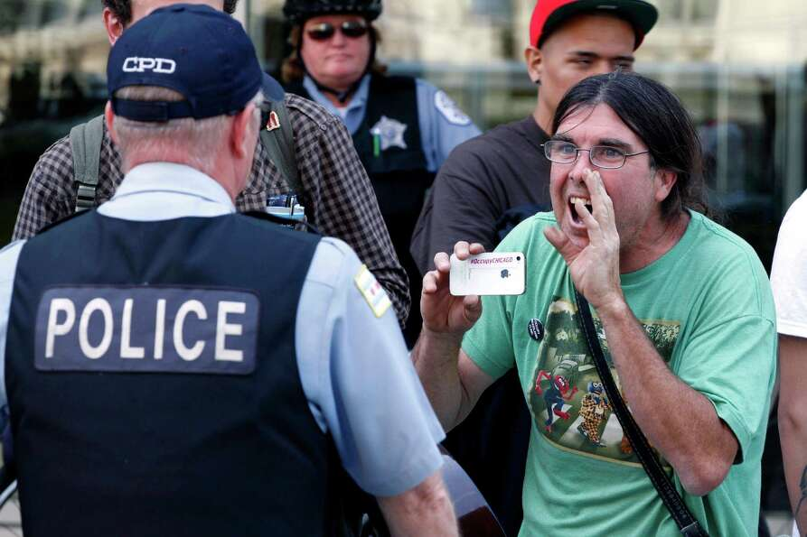 A protester yells at a Chicago police officer during a demonstration outside the federal Immigration