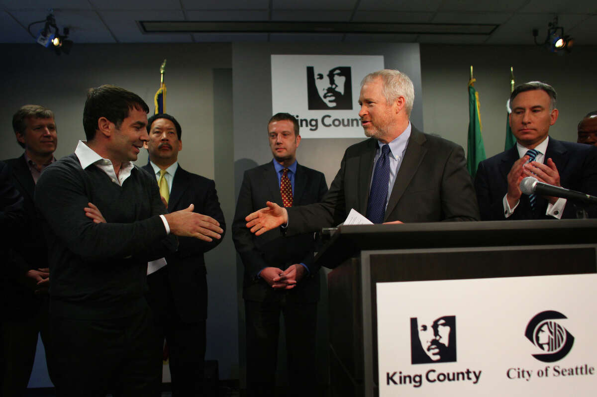 Arena investor Chris Hansen and Seattle Mayor Mike McGinn shake hands during a press conference announcing a memorandum of understanding on financing of a new NBA and NHL arena in Seattle. The memorandum is between the owners of the new arena and local government. The event was held on Wednesday, May 16, 2012 at King County's Chinook Building.