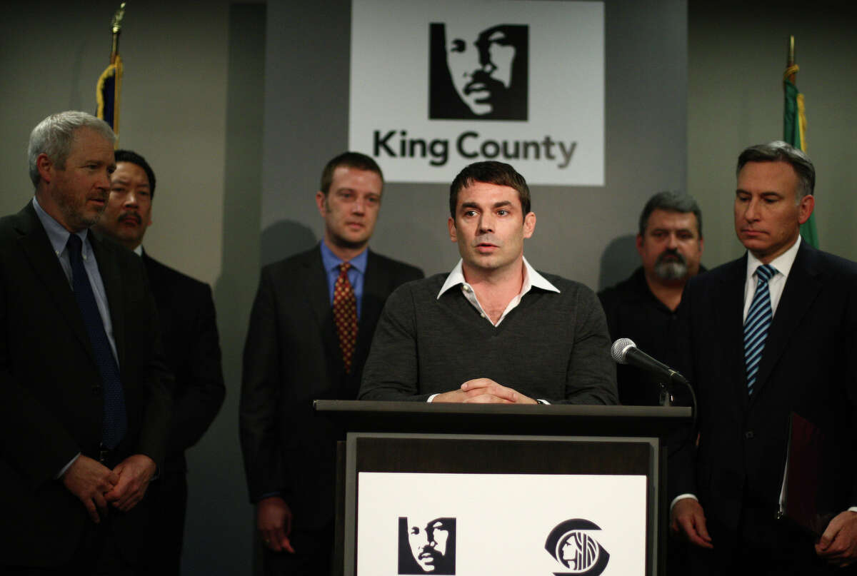 Arena investor Chris Hansen is flanked by Seattle Mayor Mike McGinn, left, and King County Executive Dow Constantine, right, during a May 16 news conference announcing a financing agreement for a new NBA and NHL arena in Seattle.