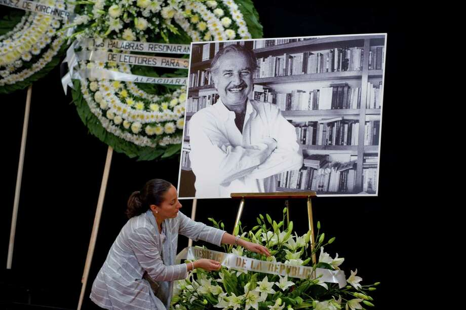 A woman straightens a wreath next to a portrait of late Mexican writer Carlos Fuentes during his wake at the Fine Art Palace on May 16, 2012 in Mexico City. Fuentes, who died on Tuesday aged 83 as a result of heart problems, was one of the Spanish-speaking world's best known writers, famous for his prolific output and his use of experimental language. Photo: ALFREDO ESTRELLA, AFP/Getty Images / AFP