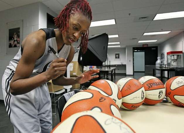 SPORTS   Danielle Robinson circles tables signing basketballs as the Silver Stars participate in media day at the AT&T Center on May 16, 2012.  Tom Reel/ San Antonio Express-News (San Antonio Express-News)