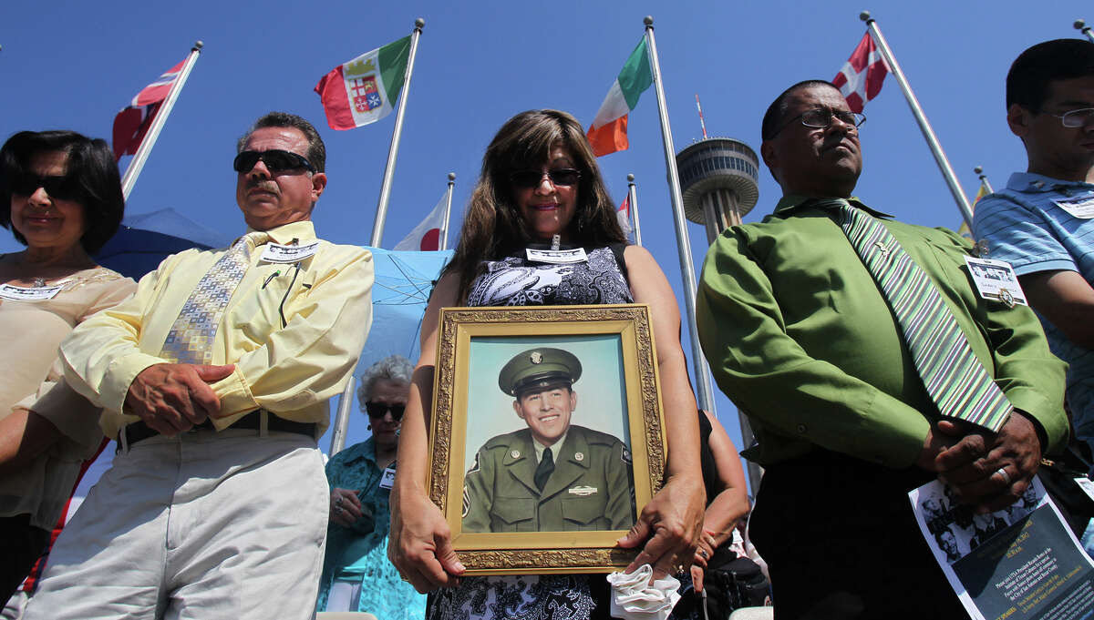 Sandy Garza Halbert (center) holds a picture of her father Army Sergeant First Class Pablo B. Garza at a ceremony on May 16, 2012 at the Institute of Texan Cultures celebrating the near completion of the Faces with Names photo collection effort. The grassroots project localizes a national effort to gather images and profiles of soldiers killed during the Vietnam War. Standing next to Halbert are Yolanda Garza Molina (far left), Roger Molina, and Pablo B. Garza's son Gabriel Garza (right, wearing striped tie). Pablo B. Garza was killed in Vietnam November 20, 1969.