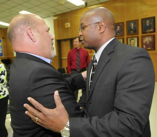 Lone finalist Timothy Chargois, right, accepts congratulations from board member Tom Neild, left, after the board had adjourned.  Beaumont ISD trustees met in a special meeting to name a lone finalist to replace retiring superintendent Carrol Thomas Monday night. Dave Ryan/The Enterprise Photo: Dave Ryan