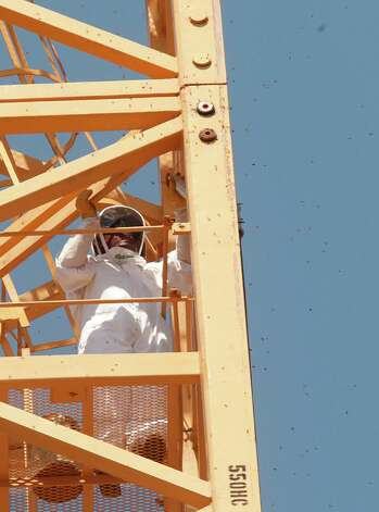 Gotcha Pest Control Technician treats the area where bees were found making a home inside the pipes of a crane at a high rise construction site along 5300 block of Brownway St. in the Galleria area on Wednesday, May 16, 2012, in Houston. Photo: Mayra Beltran, Houston Chronicle / Houston Chronicle