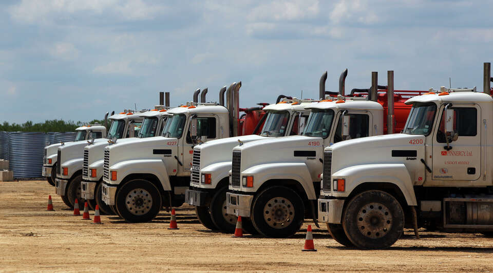 Waste water trucks used by Pinnergy, Ltd. are lined up on recently developed commercial land near Pl