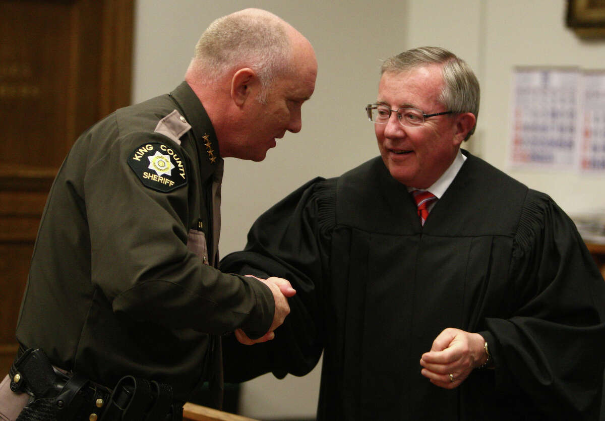 King County Sheriff Steve Strachan is congratulated by King County Superior Court Judge Richard McDermott on Wednesday after a swearing-in ceremony.