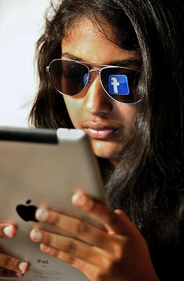 The 'Facebook' logo is reflected in a young Indian woman's sunglasses as she browses on a tablet in Bangalore on May 15, 2012.  World's popular and leading social networking company Facebook Inc., founded in a Harvard dorm room by Mark Zuckerberg whose current value exceeds 100 billion USD, will be making an initial public offering (IPO) which is slated to be Silicon Valley's biggest-ever.  AFP PHOTO/Manjunath KIRANManjunath Kiran/AFP/GettyImages Photo: Manjunath Kiran, AFP/Getty Images