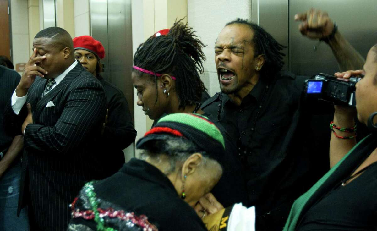 Activist Quanell X, left, and other African-Americans react to the outcome of the first of four trials in the police beating of Chad Holley, a black teen arrested for burglary in 2010.