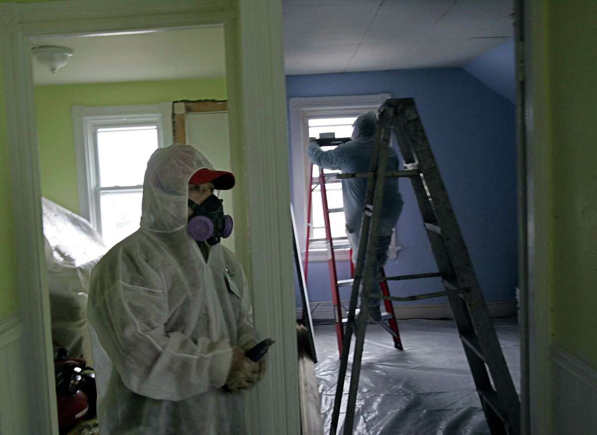 FILE - In this Thursday, Feb. 23, 2006 photo, contractors Luis Benitez, foreground, and Jose Diaz, background, clean up lead paint in a contaminated building in Providence, R.I. Albany and Schenectady received $6.9 million in 2020 from the federal government to do lead abatement in their communities. (AP Photo/Chitose Suzuki)