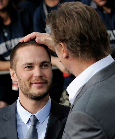 "Taylor Kitsch (left), a cast member in the film ""Battleship,"" gets a rub on the head from fellow cast member Liam Neeson at the American premiere of the film, Thursday, May 10, 2012, in Los Angeles. The film is released in theaters this Friday, May 18. Photo: Chris Pizzello, Associated Press"