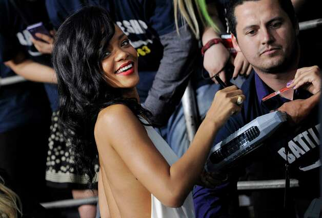 "Rihanna, a cast member in ""Battleship,"" turns back for photographers as she signs autographs at the premiere of the film, Thursday, May 10, 2012, in Los Angeles. The film is released in theaters this Friday, May 18. Photo: Chris Pizzello, Associated Press"