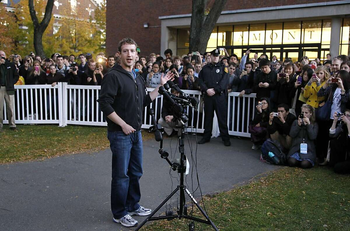 Facebook creator Mark Zuckerberg takes questions from members of the media as a crowd looks on on the campus of Harvard University, in Cambridge, Mass., Monday, Nov. 7, 2011.
